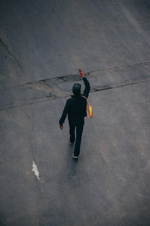 man in black hoodie and black pants walking on gray asphalt road during daytime