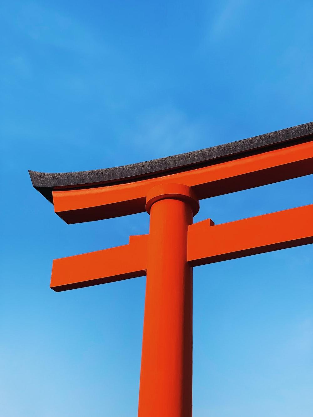 orange and black cross under blue sky during daytime