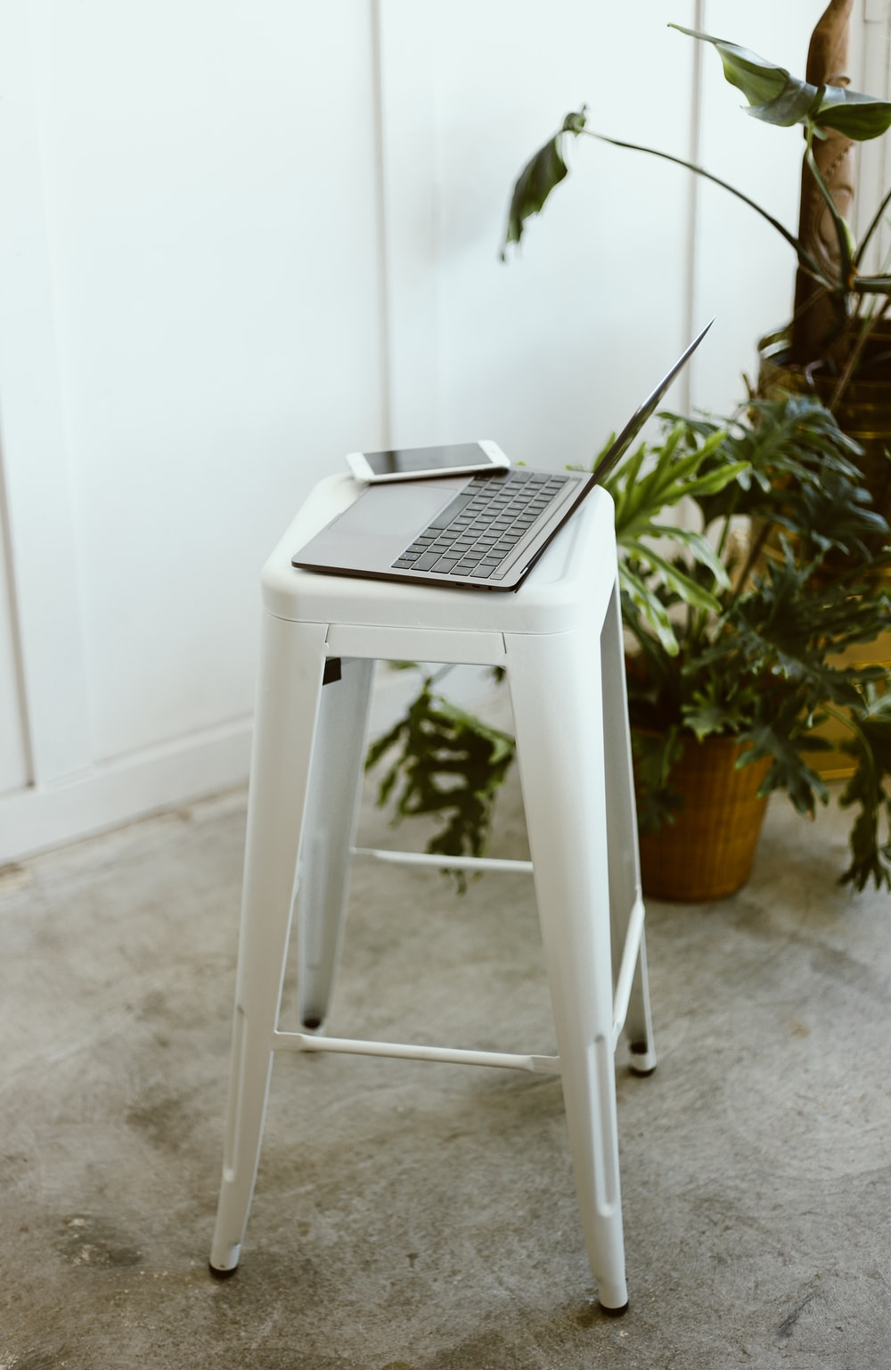 macbook pro on white plastic stool