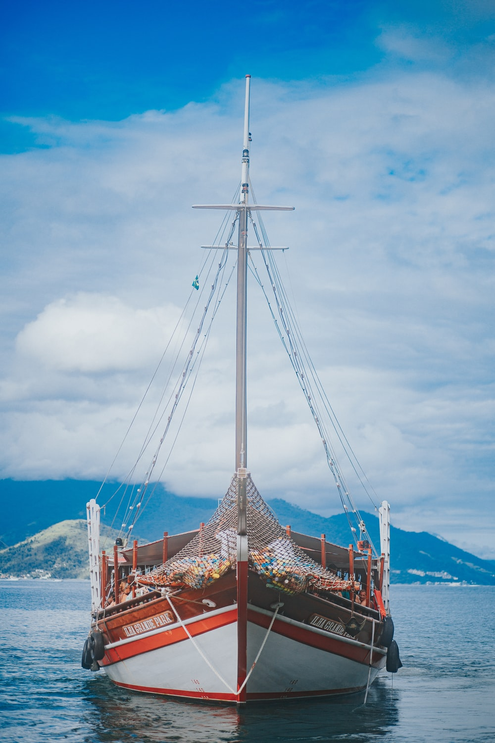 brown wooden boat on sea under white clouds and blue sky during daytime
