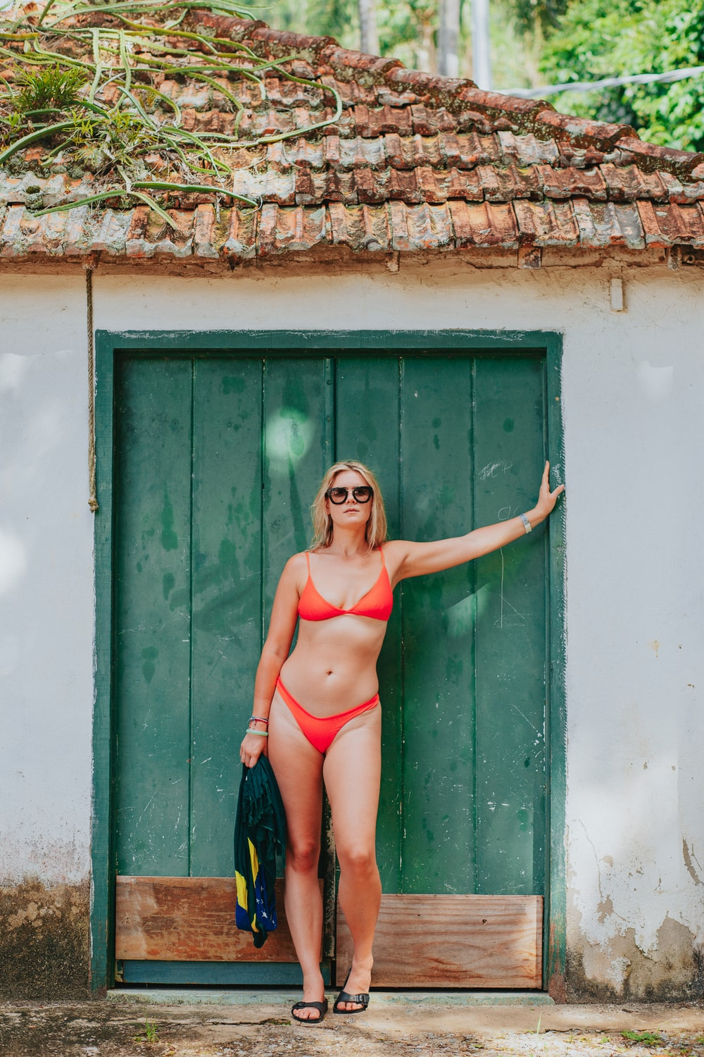 woman in red bikini standing beside green wooden door