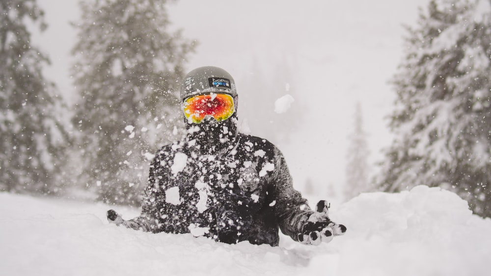 person in black jacket and orange helmet on snow covered ground during daytime