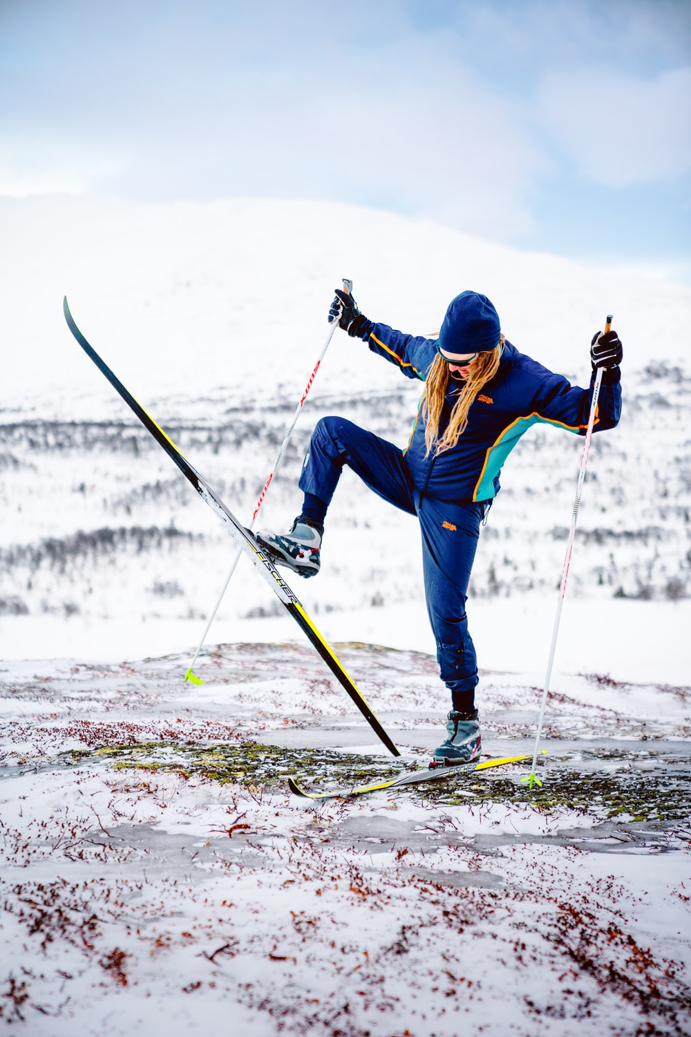 man in blue jacket and blue pants riding on ski blades on snow covered ground during