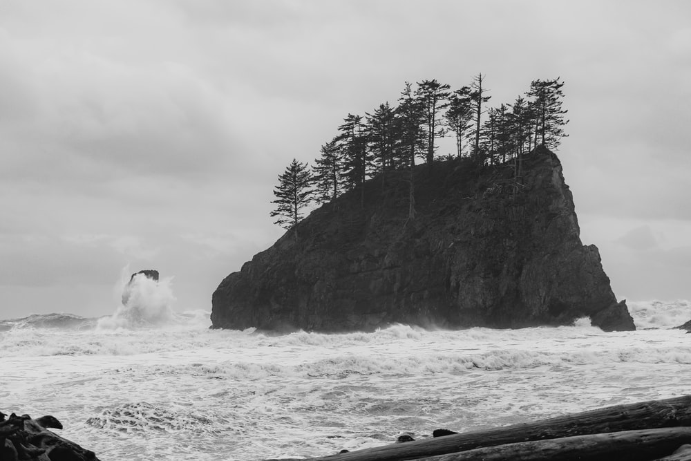 grayscale photo of man and woman standing on rock formation near body of water