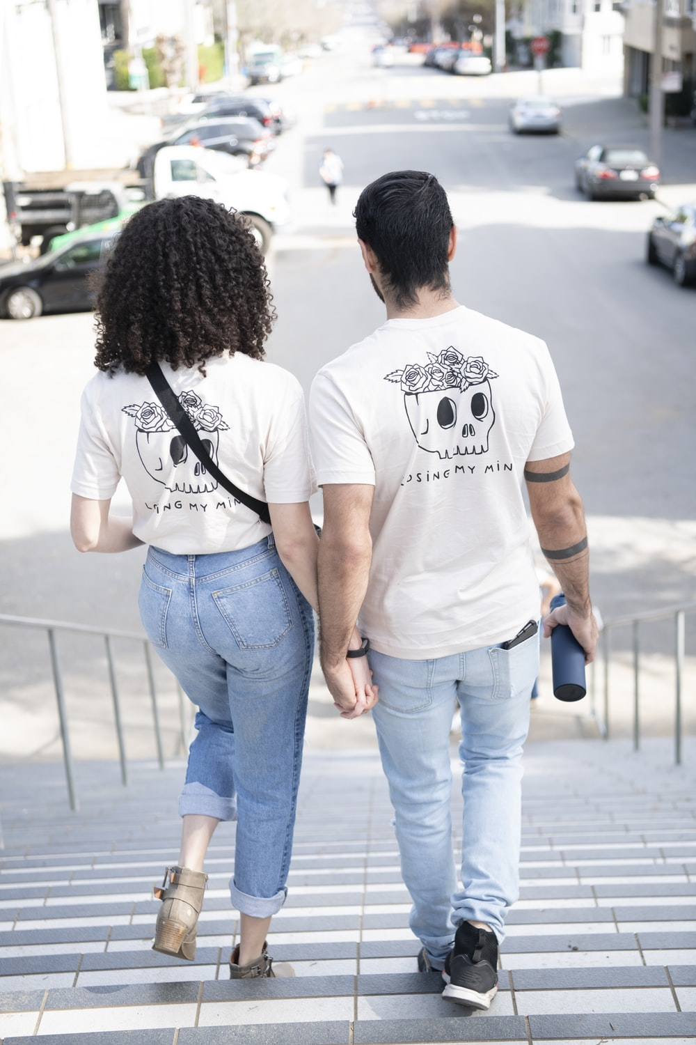 man in white crew neck t-shirt and woman in blue denim jeans walking on sidewalk