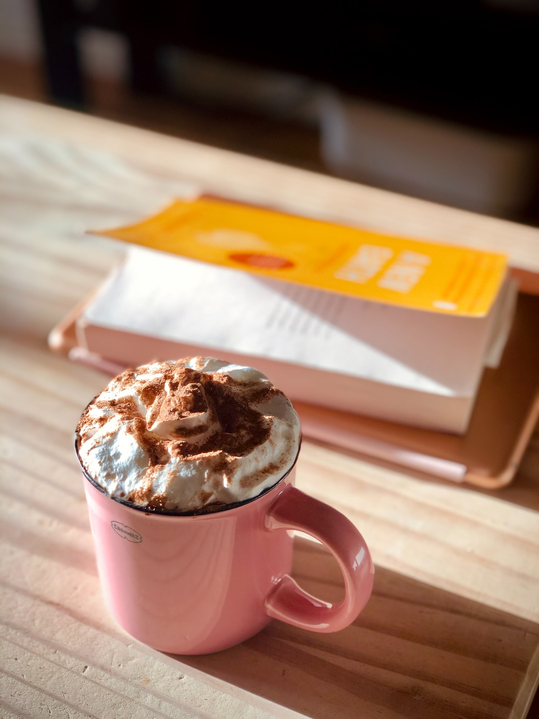 A pink mug of hot chocolate with cream and chocolate powder dusting.