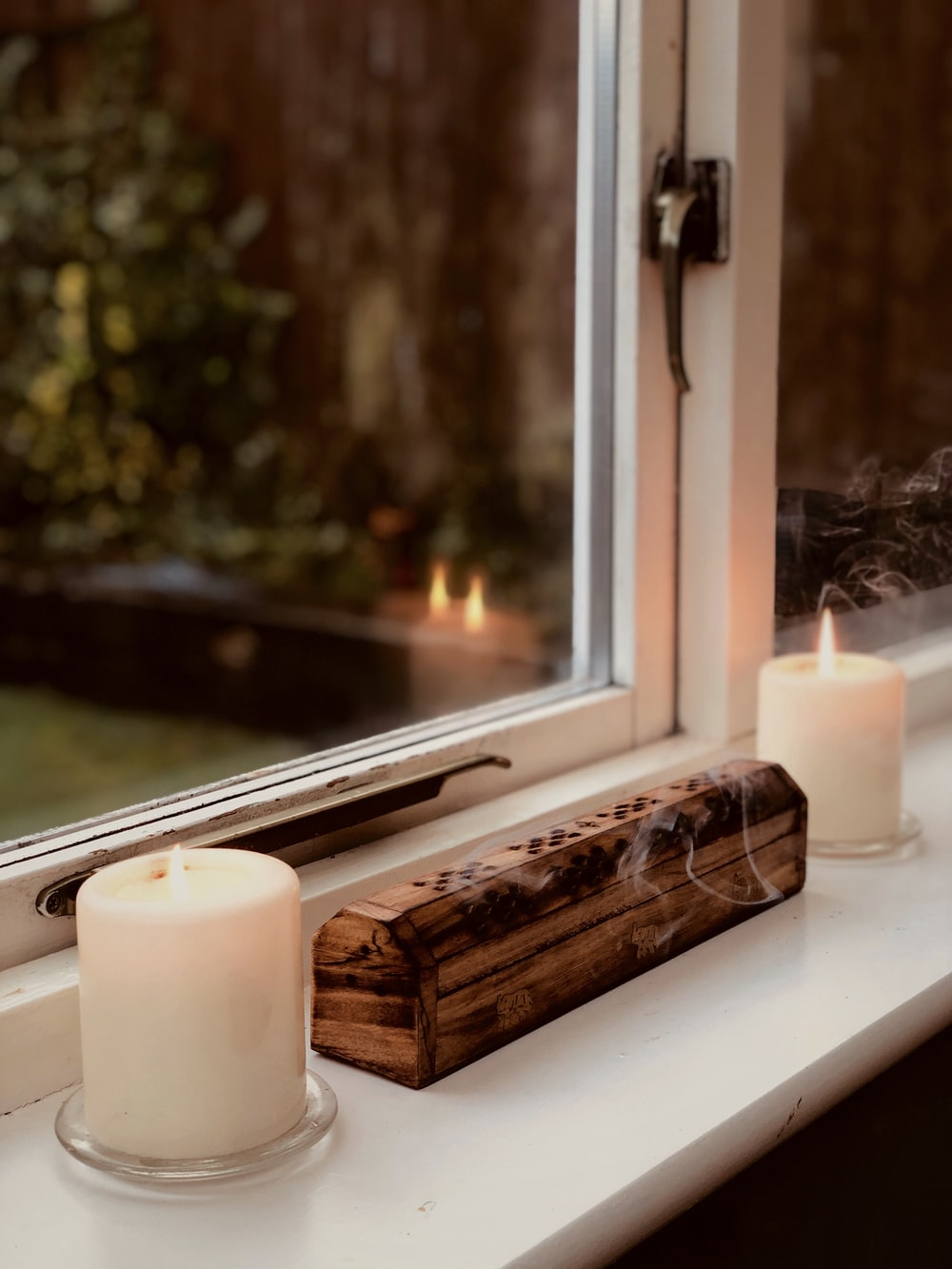 white pillar candle beside window