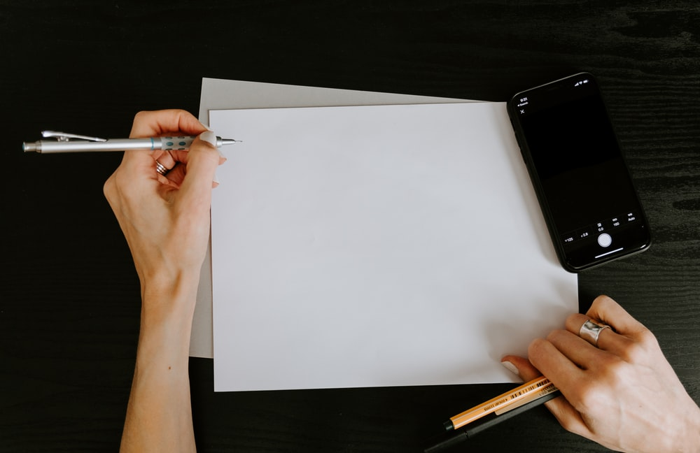 白い紙に書いている人