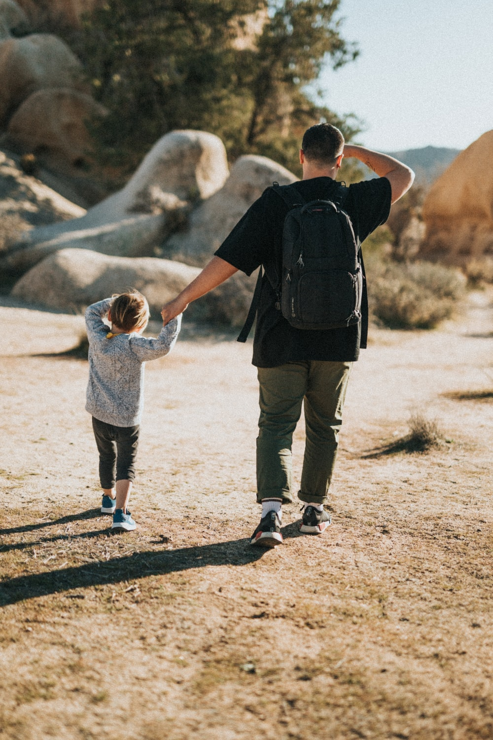 man in black t-shirt holding child in gray hoodie