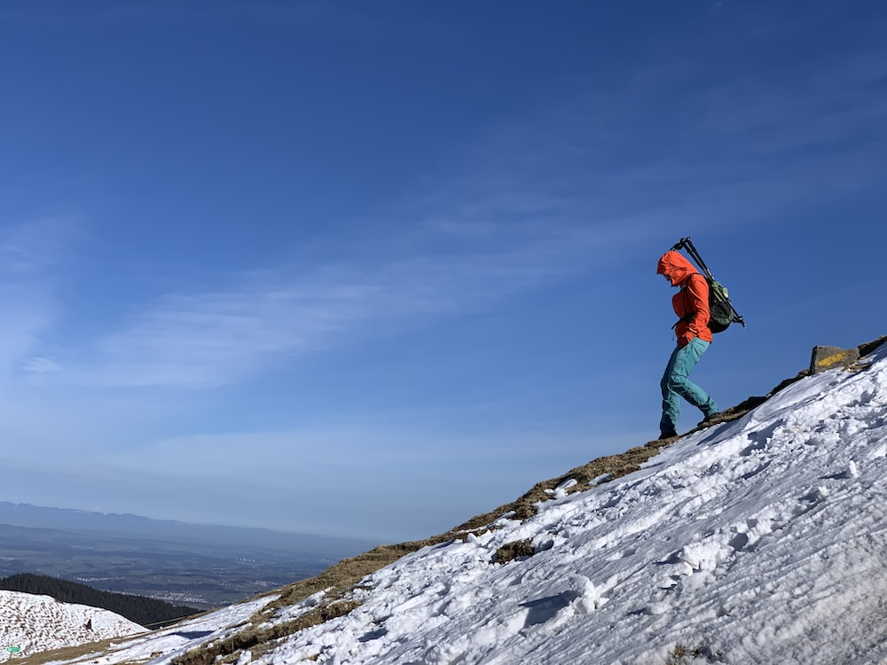 person in red jacket and black pants standing on snow covered mountain during daytime