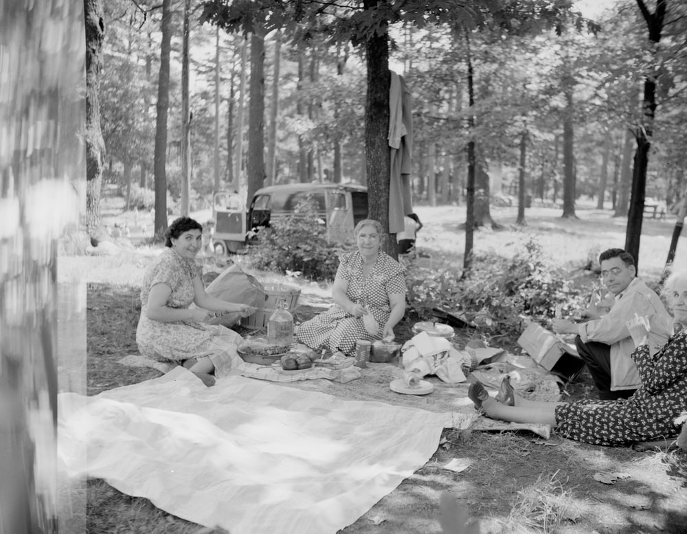 grayscale photo of people sitting on ground