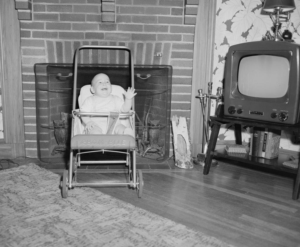 grayscale photo of baby sitting on stroller