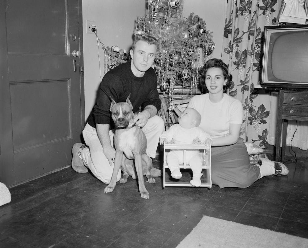 grayscale photo of boy sitting beside dog on floor