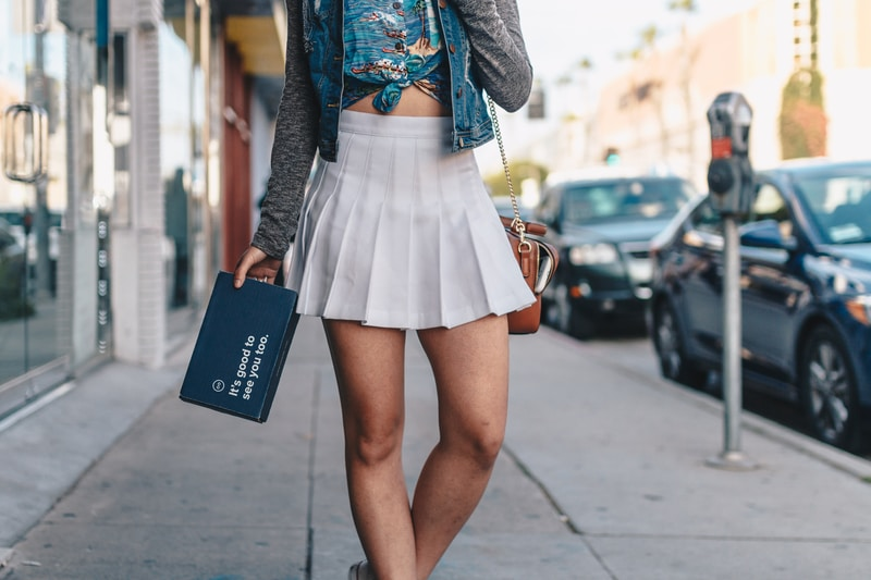 woman in gray cardigan and white skirt standing on sidewalk during daytime