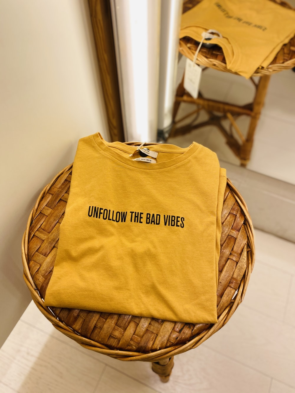 yellow and black crew neck shirt on brown woven chair