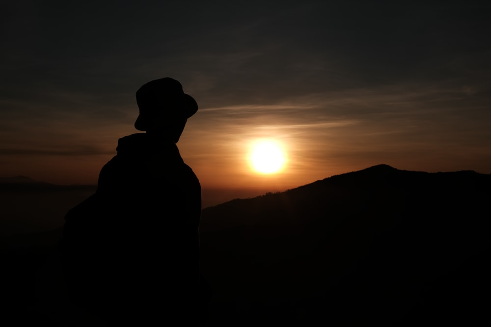 silhouette of man standing on mountain during sunset