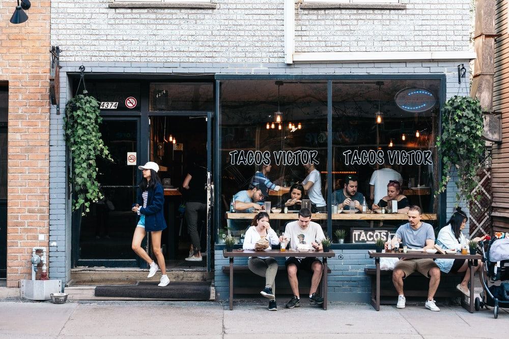 people sitting on bench in front of the coffee shop during daytime