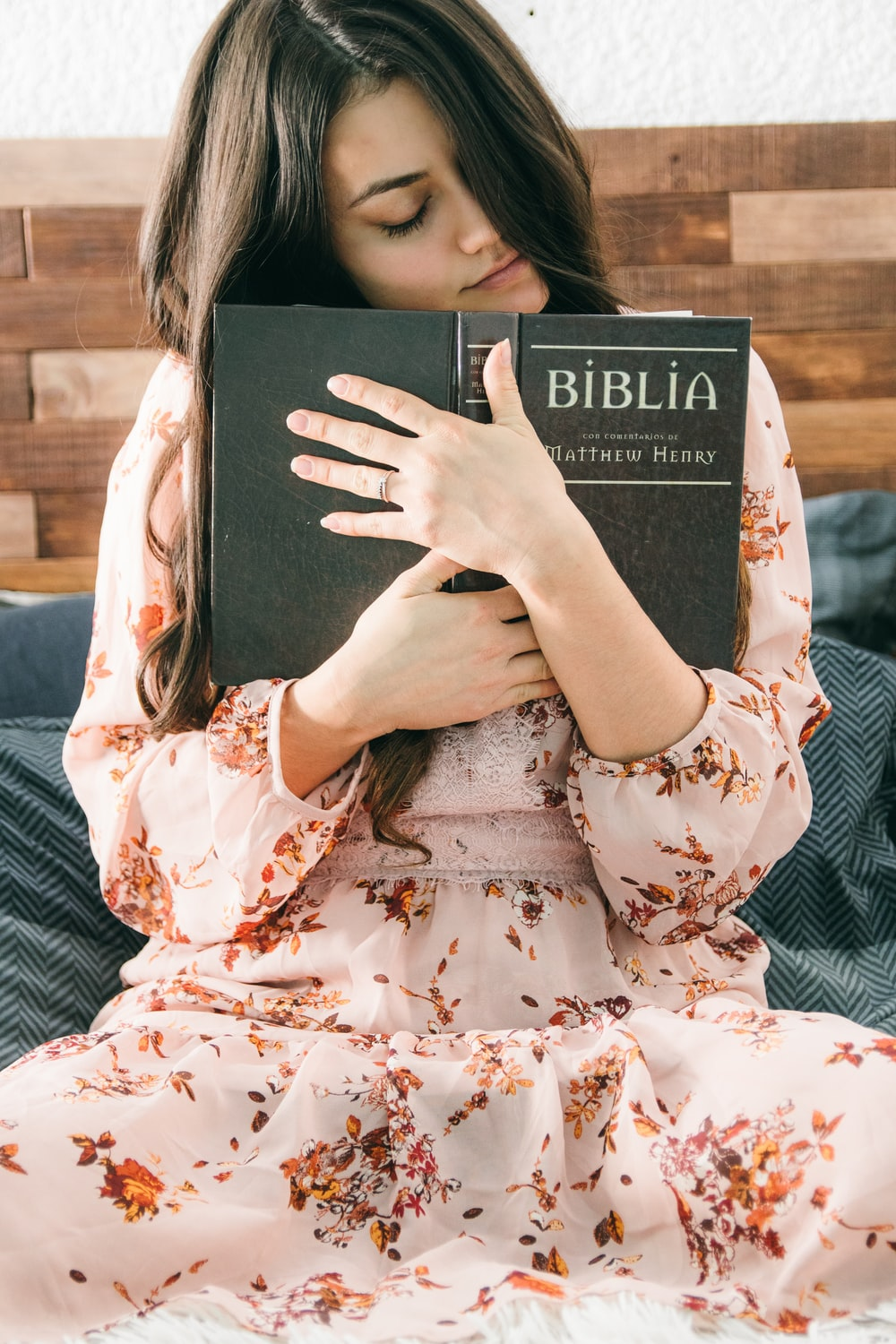 woman in white and red floral dress holding black book