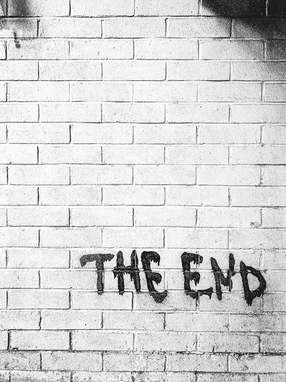 white brick wall with black and white graffiti