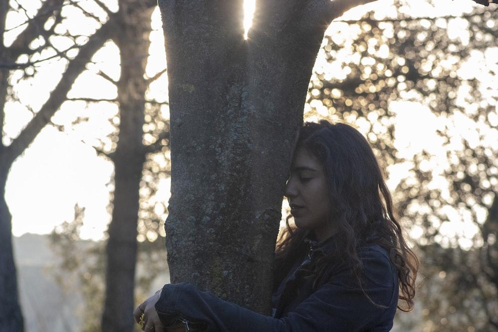 woman in blue jacket leaning on tree