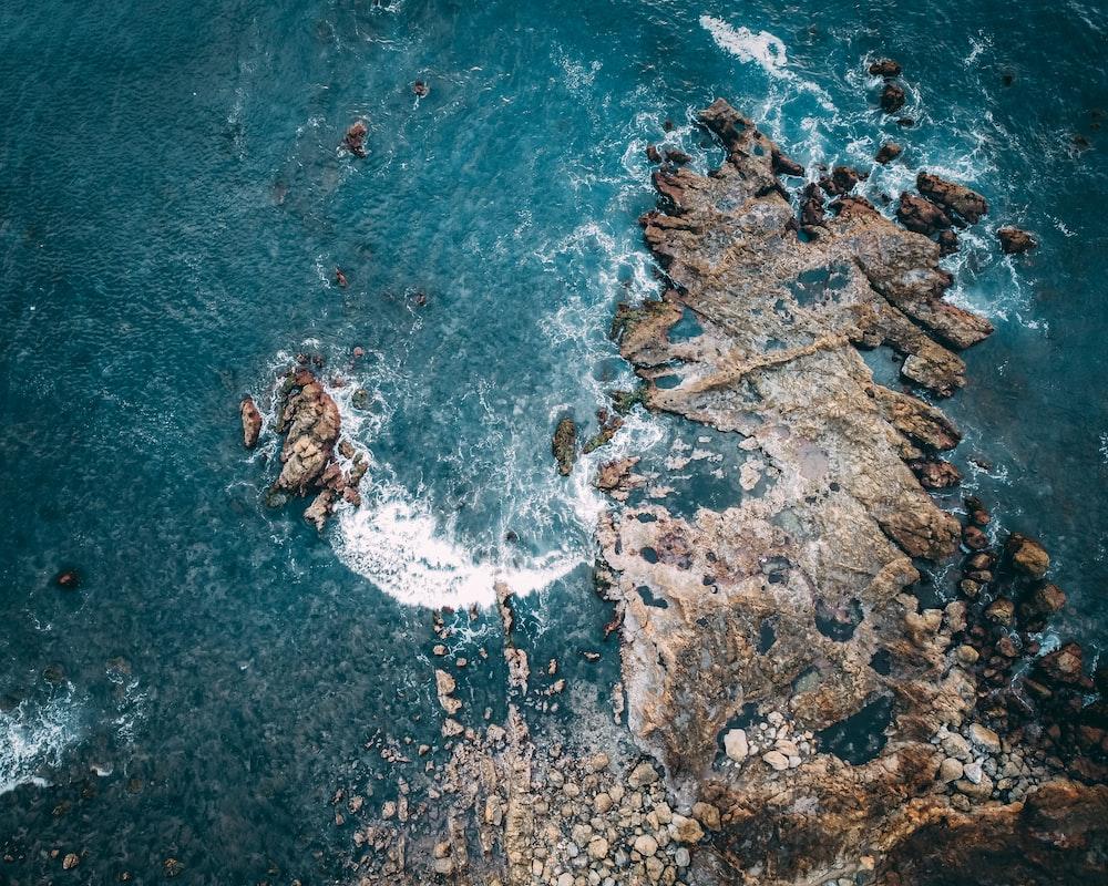 aerial view of ocean waves crashing on rocks during daytime