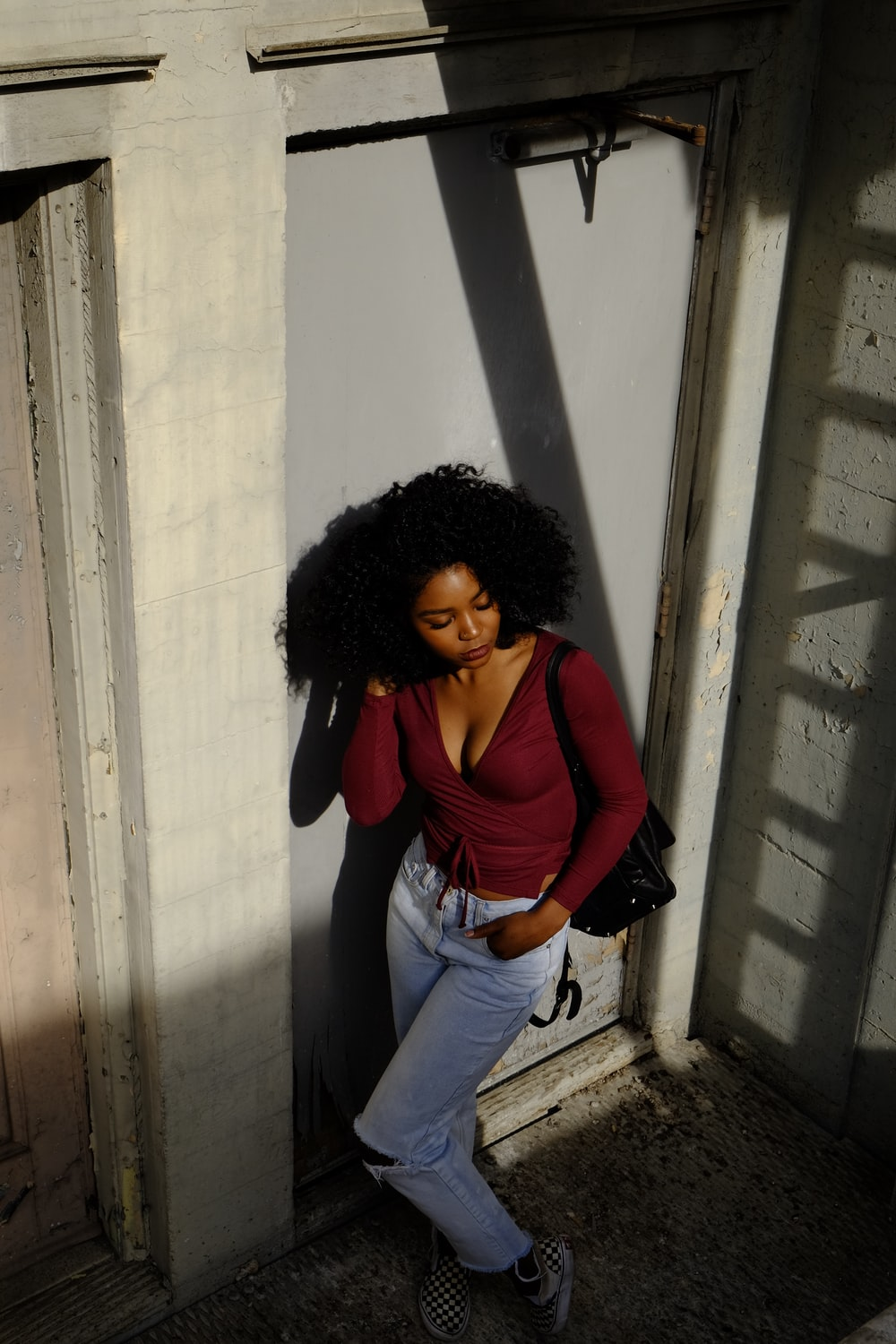 woman in red long sleeve shirt and blue denim jeans leaning on wall