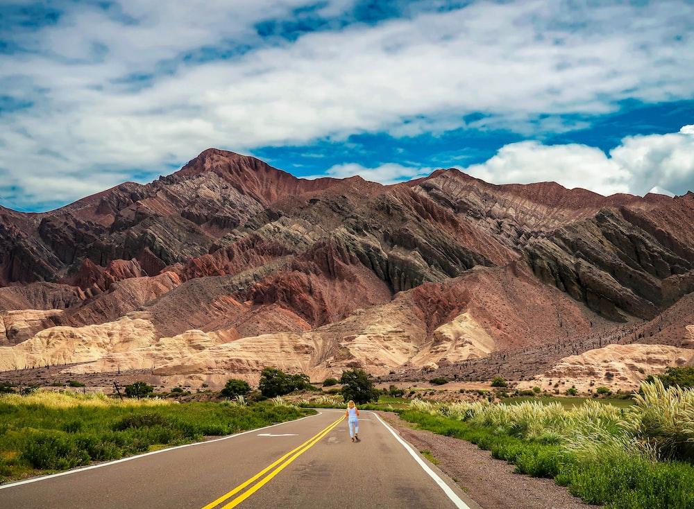 gray asphalt road in between brown mountains under blue sky during daytime
