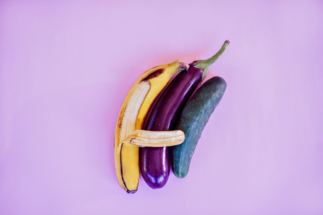 An erotic composition of fruits and vegetables: banana, eggplant and cucumber representing threesome and polyamory in erotic context. Great for sex education as safe for web picture.