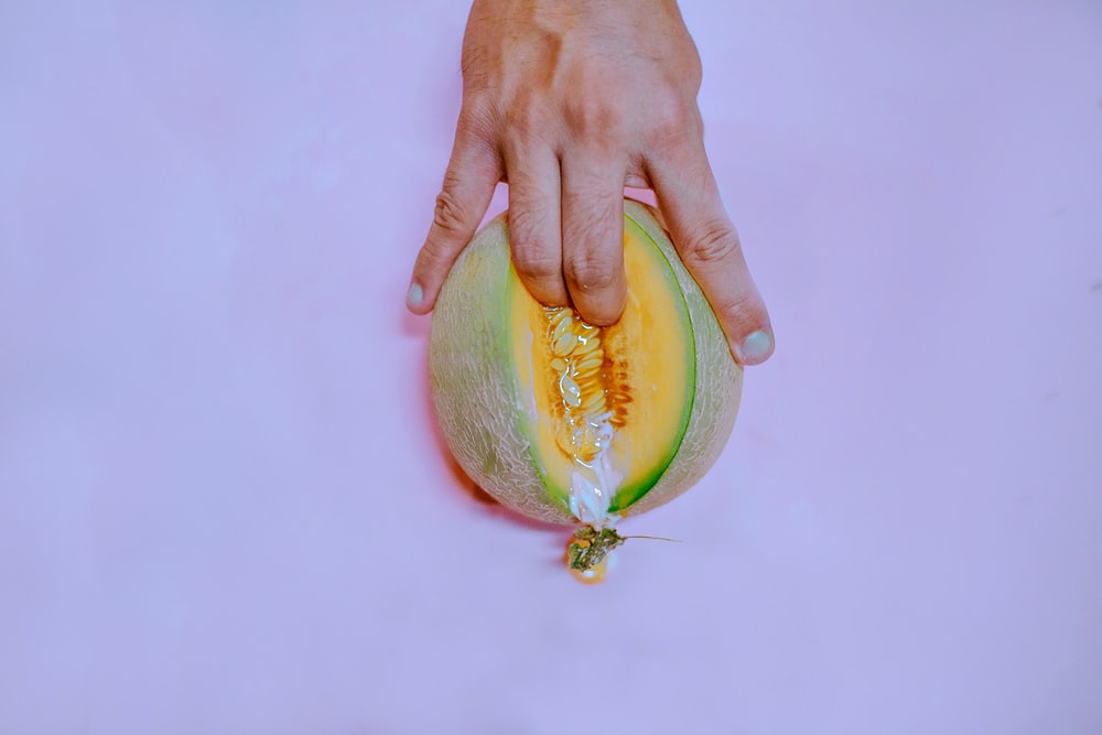 person holding coconut fruit with yellow fruit