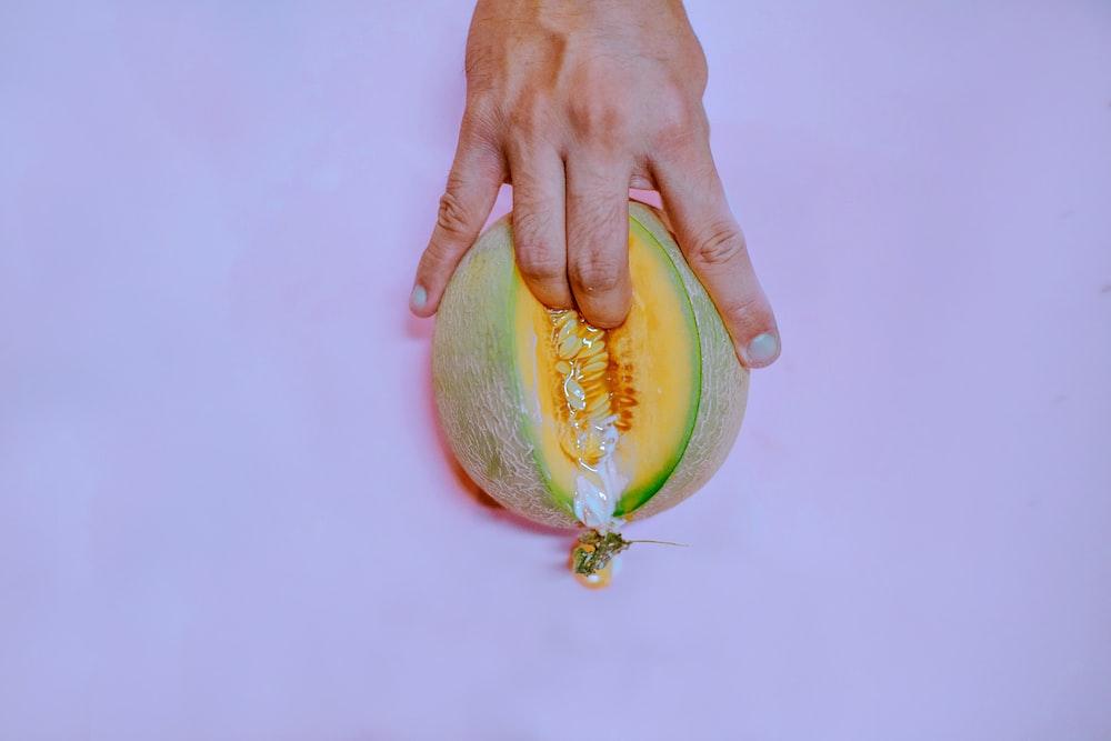 manos dentro de una fruta como representación de que el orgasmo femenino requiere de un calentamiento previo