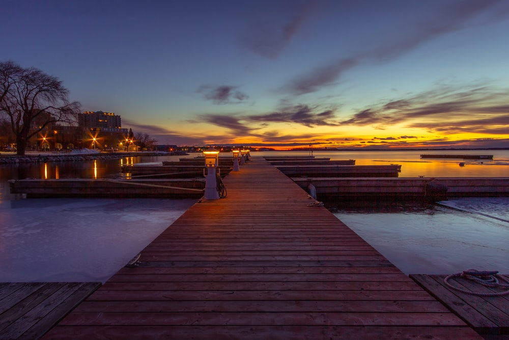 brown wooden dock during sunset