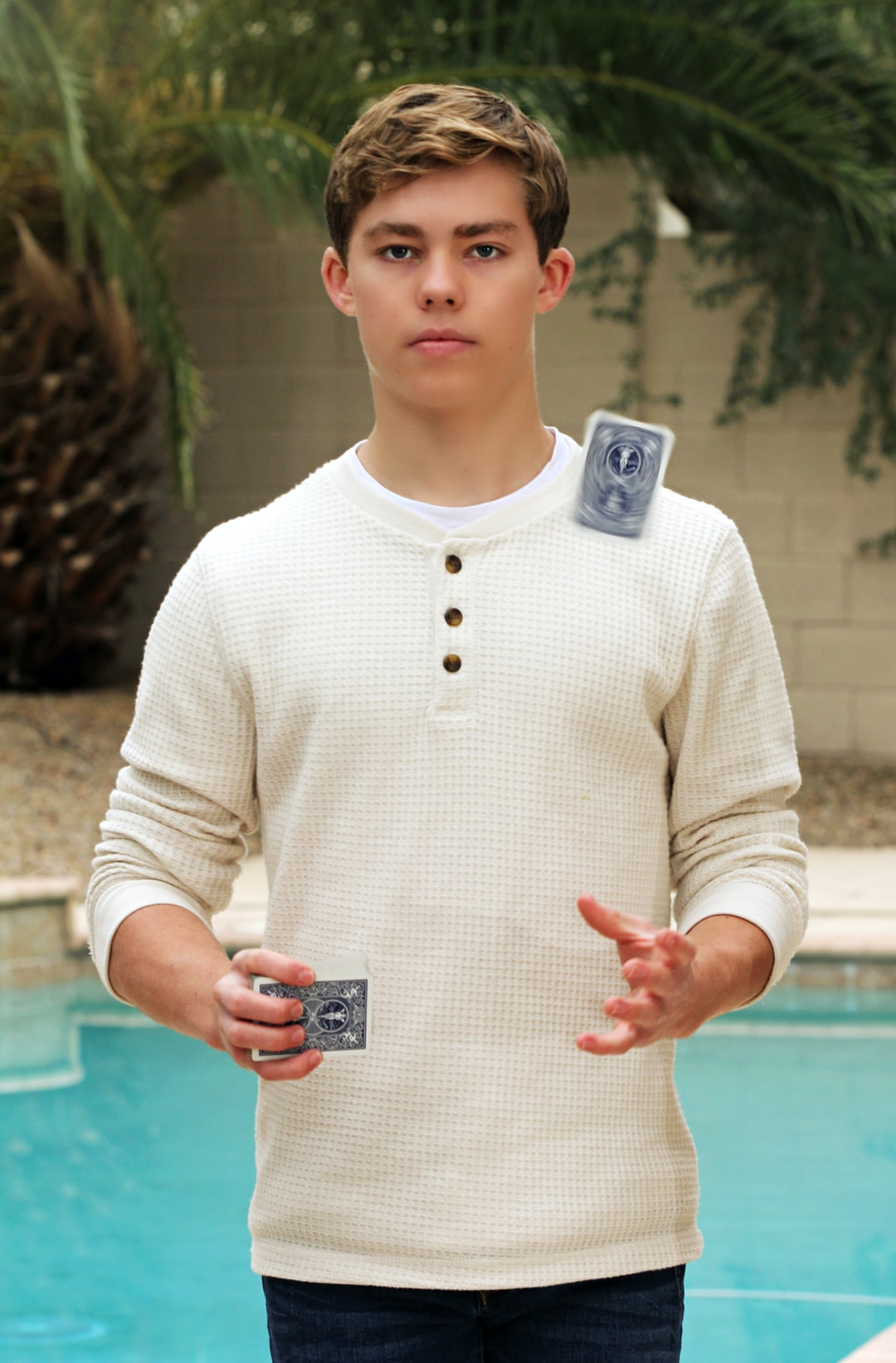 A boy juggles blue cards.