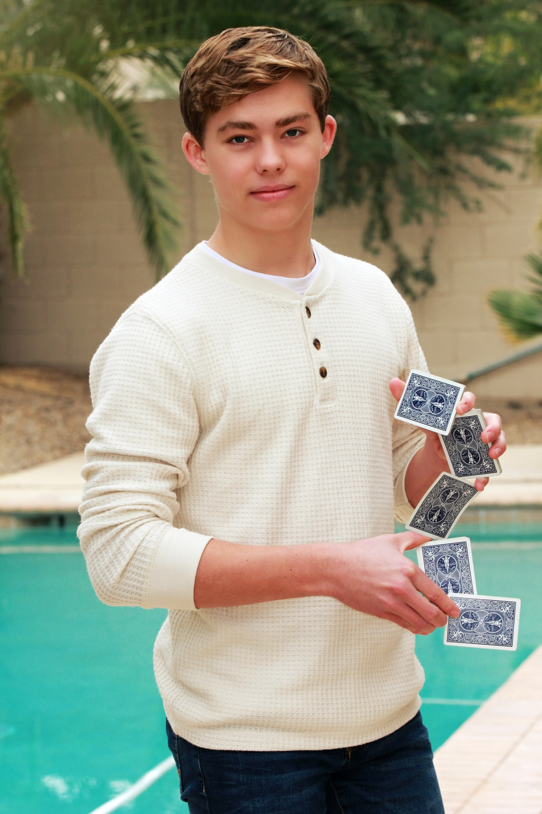 A boy holds cards in a difficult position.