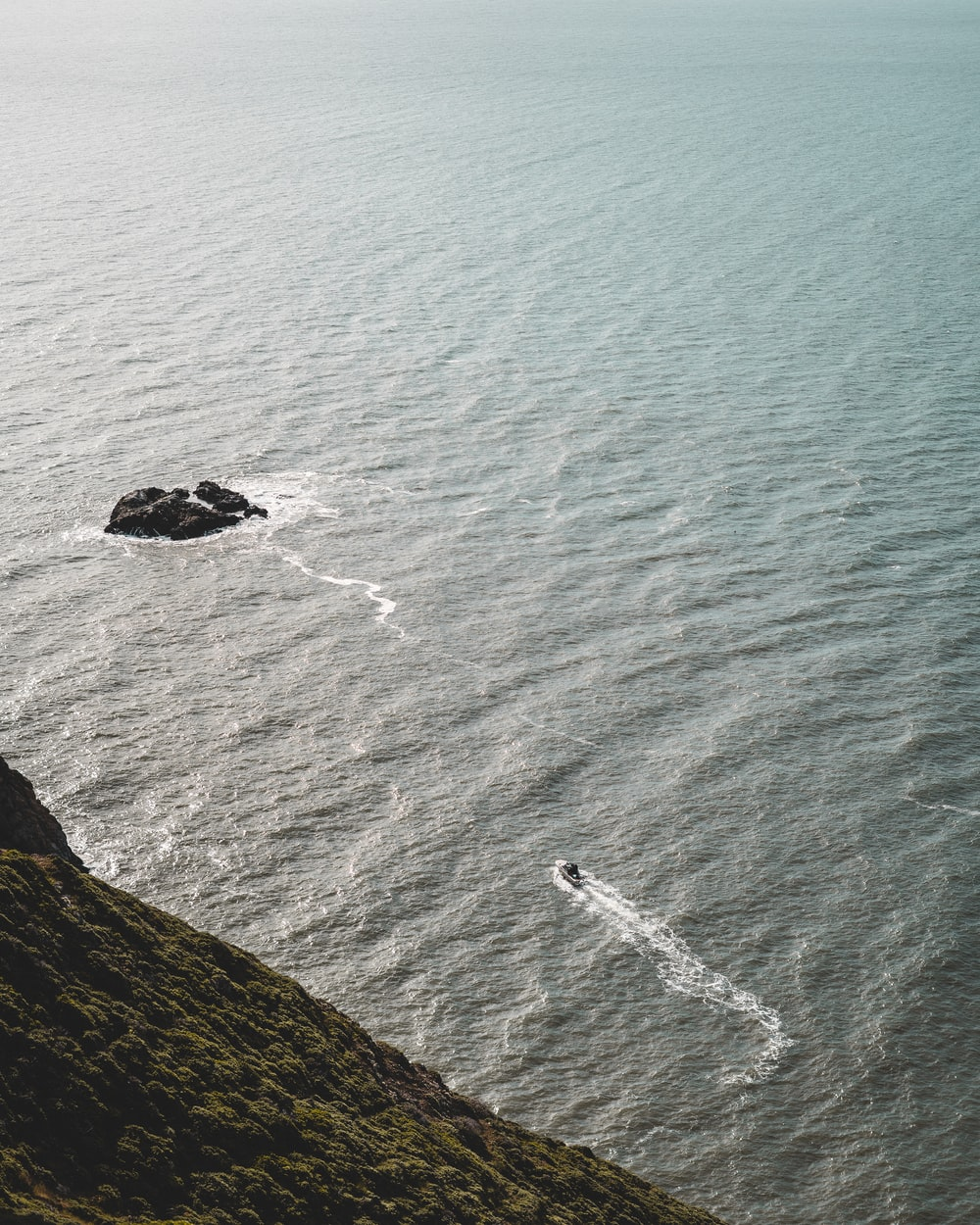 aerial view of ocean waves crashing on rock formation during daytime