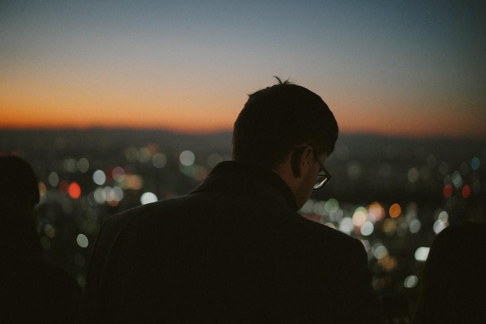 man in black suit jacket during sunset
