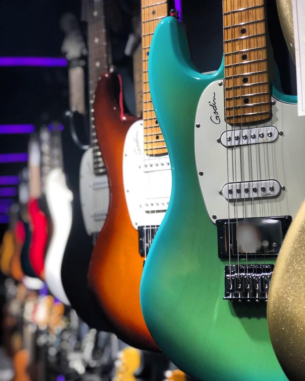white and orange electric guitars
