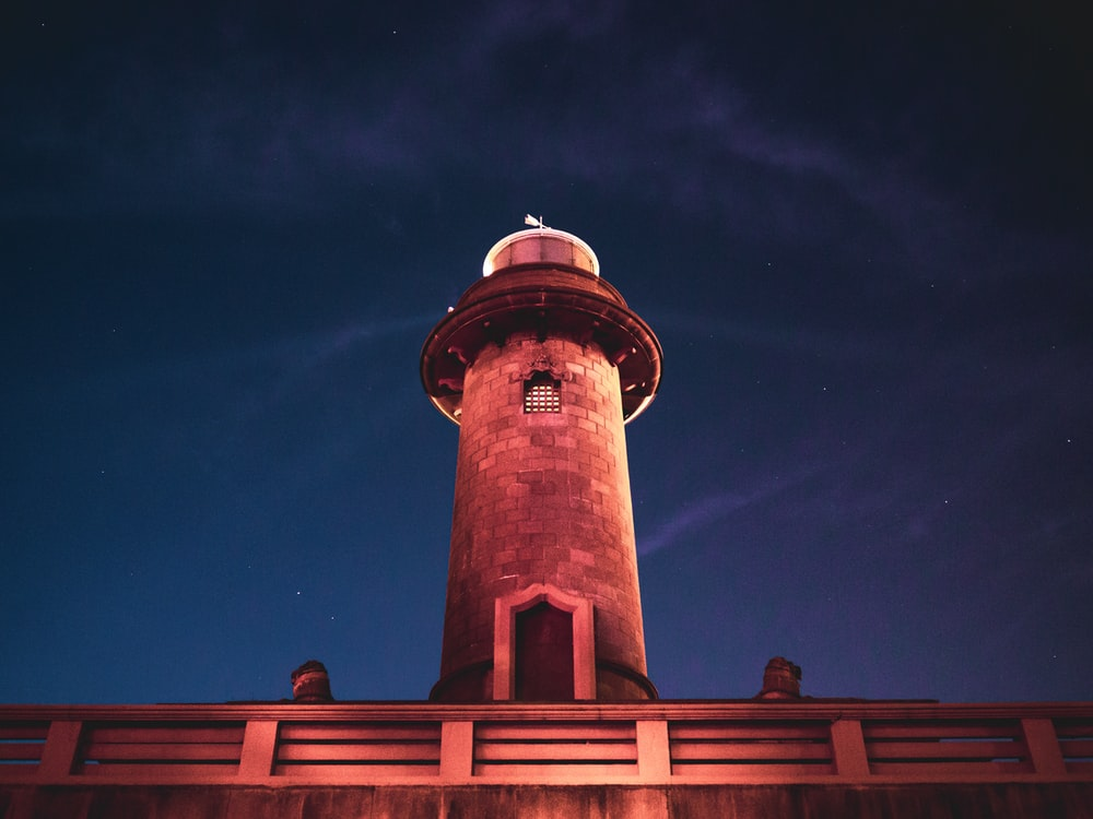 brown and white concrete tower under blue sky during night time