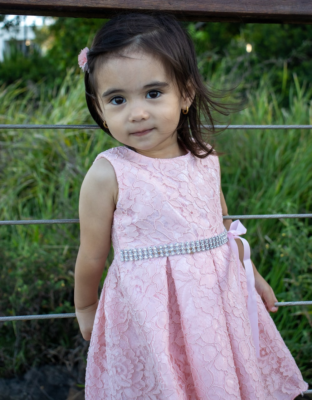 girl in pink sleeveless dress standing near gray metal fence during daytime