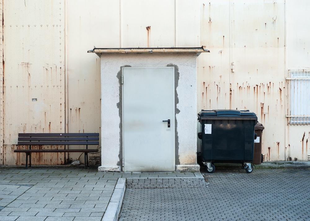 black trash bin beside white wall