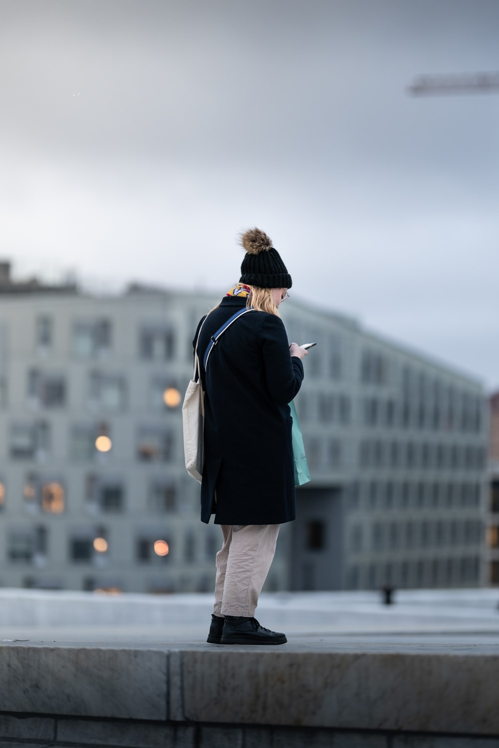 woman in black coat and gray pants standing on gray concrete floor during daytime