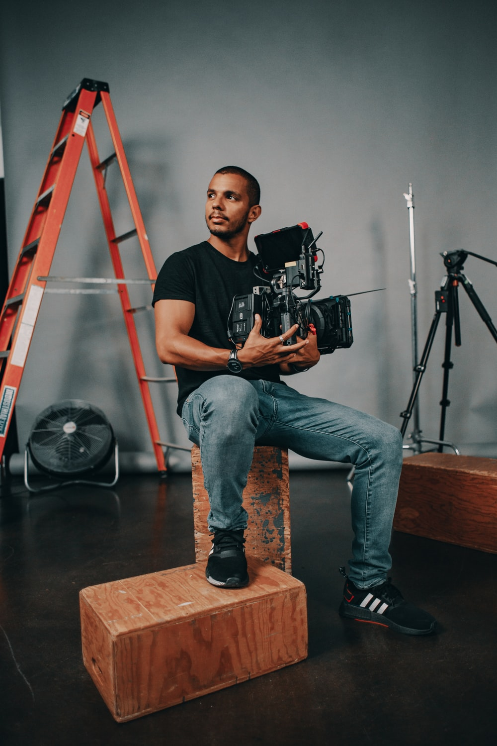 man in black crew neck t-shirt and blue denim jeans sitting on brown wooden stool