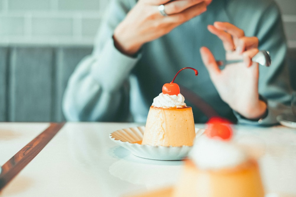 person holding cupcake with white icing on white round plate