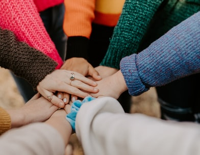close up of 8 hands piled atop each other in a circle, each person wears a different colour jumper