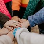 person igirl friends hands piled togethger