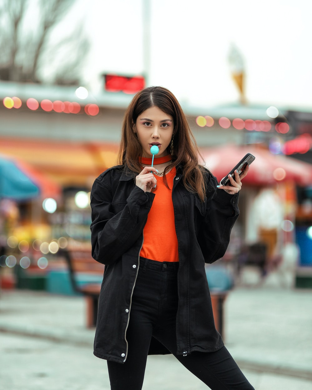 woman in red blazer holding smartphone