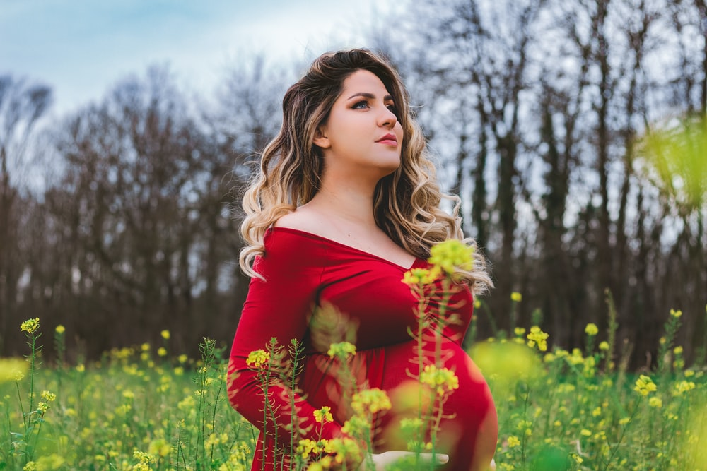 woman in red off shoulder dress holding yellow flowers
