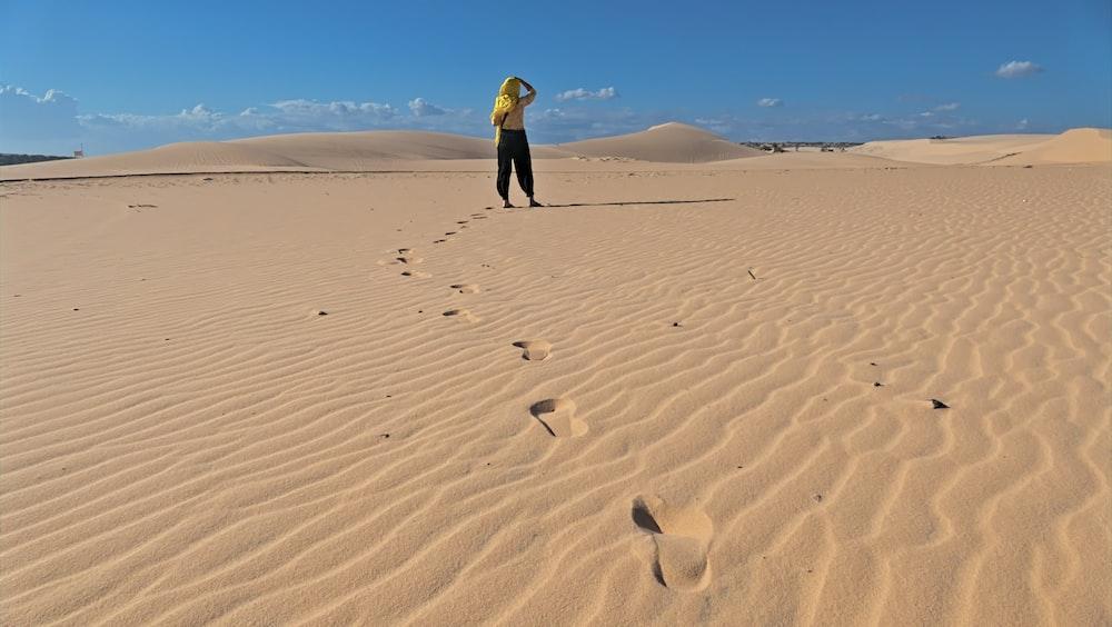 man in yellow jacket walking on sand during daytime