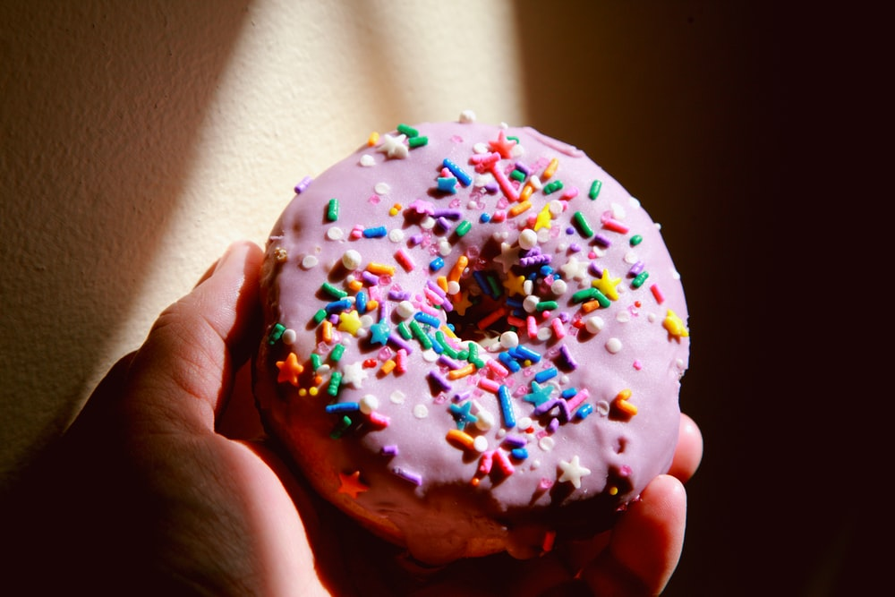 person holding white and brown doughnut