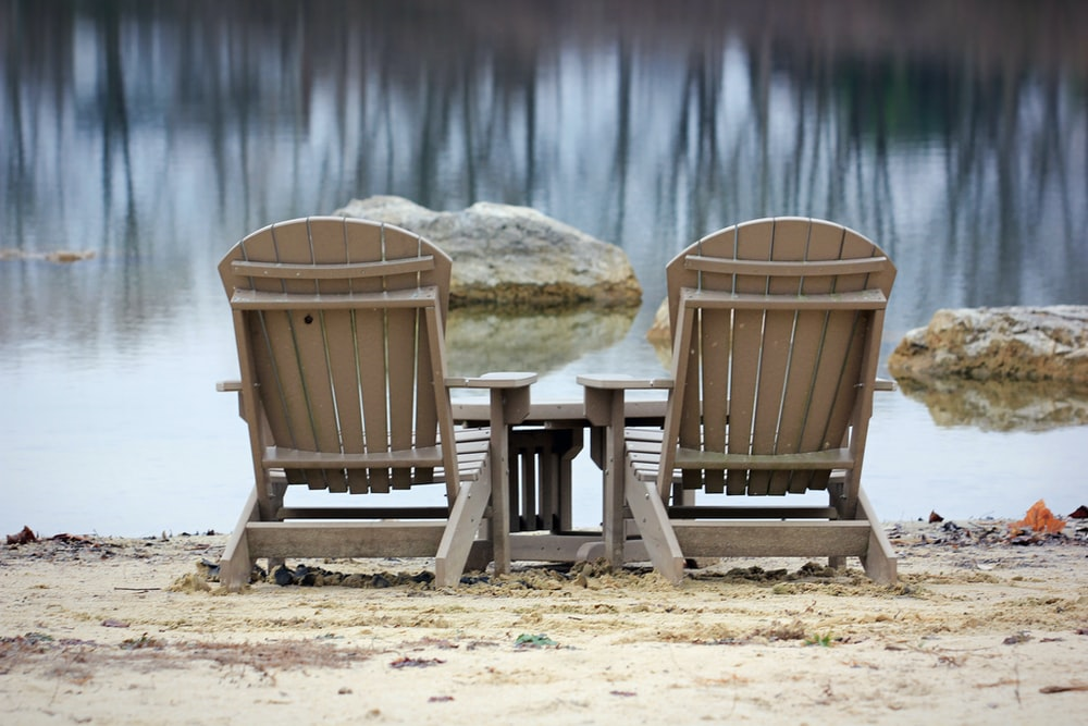 two brown wooden armchairs on white snow covered ground near body of water during daytime
