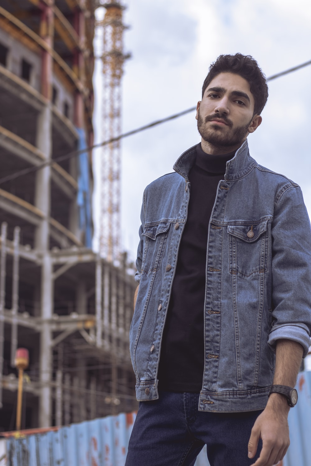 man in blue denim jacket standing near building during daytime